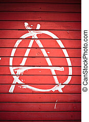 Anarchy sign painted on red wall in white color.