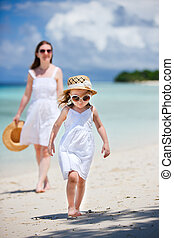 Mother and daughter at beach - Adorable little girl and her...