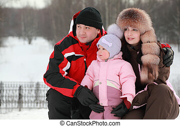 father hugs mother and little daughter at snow, they looks into distance, winter, focus on girl
