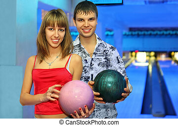 Fellow and girl stand alongside with balls for bowling during rest in club, focus on girl