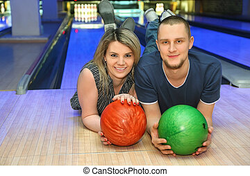 Girl and man lie on parquet in club and hold balls for bowling, focus on woman