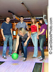 Girl prepares for throw ball in bowling and friends hearten...