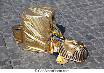 fake golden mask pharaoh lies on stones of pavement,...