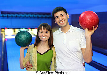 Man and young woman hug and in free hand hold  ball for bowling