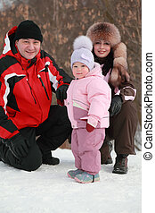 father, mother and little daughter at snow, winter, nature, focus on girl