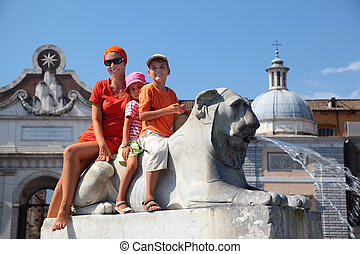 young mother, young daughter and son are sitting astride fountain in form of lion on Piazza del Popolo in Rome, Italy