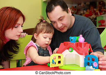 mother and father playing with his little daughter, toy house, focus on girl