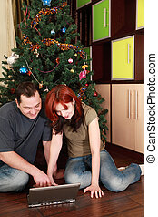 young wife and husband sitting on floor near Christmas tree, looking at laptop's screen and smiling, focus on woman
