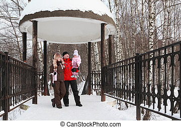 father, mother and little daughter standing in rotunda, snow, winter