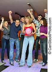 Woman prepares for throw ball in bowling and friends it...