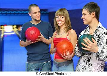 Two men holds  balls for bowling and look at girl in center, focus on youth on left and girl in center