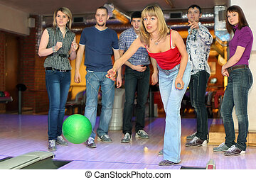 Girl throw ball on lane for bowling and friends worry for...