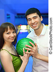 Fellow and girl turned to each other and hold one ball for bowling, focus on man