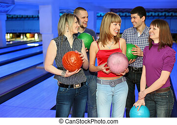 Five friends stand with balls for bowling and look on each other, focus on girl in center and on right