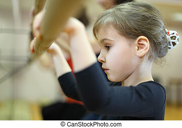 serious face of little girl in ballet class near frame and...