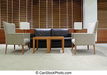 sofa, armchairs and table in light, clean and empty office;...