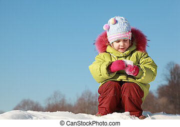 little girl in green jacket sitting at snow outdoors at winter and keep snow, trees far away
