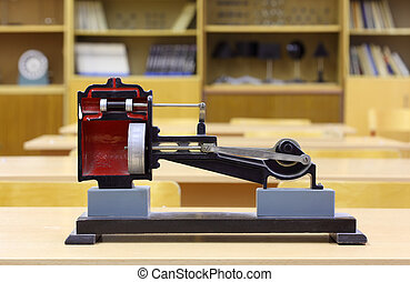 Model of steam engine on yellow desk in empty physics school...