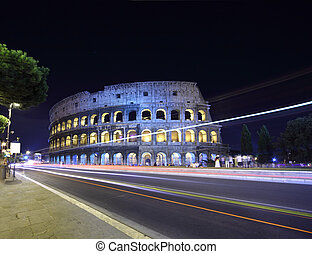 road near old stone walls of Coliseum at summer night in...