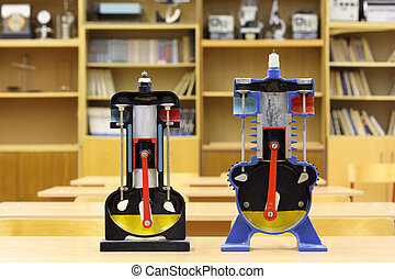 Two models of internal combustion engine on desk in empty...