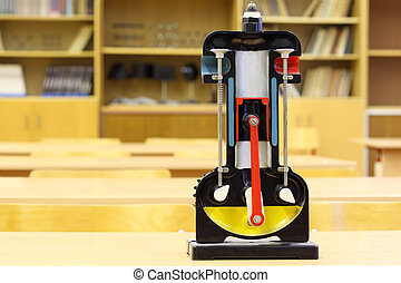 Model of internal combustion engine on desk in empty physics...