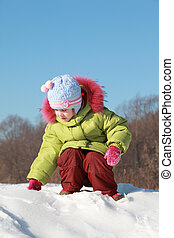 little girl in green jacket sitting at snow outdoors at winter and touches snow, trees far away