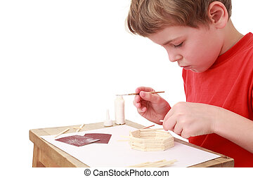 little boy in red T-shirt crafts at small table, glue, side view