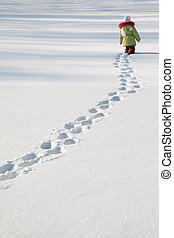little girl in green jacket walking on snow, footprints in...