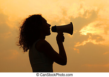 beautiful woman holding megaphone and shouted into it at sunset
