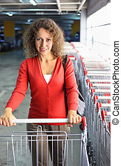 beautiful young woman with cart standing in indoor car park, row of shop carts