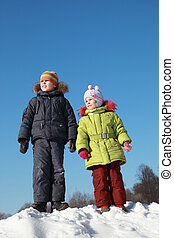 little girl in green jacket and boy standing at snow outdoors at winter and looking away