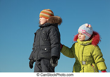 little girl in green jacket and boy standing at snow  and looking away outdoors at winter, girl clings to boy's hand