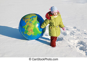 beautiful little pensive girl drags big inflatable globe on outdoors in winter