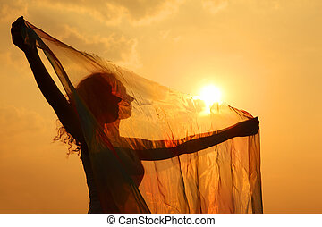 silhouette of woman with transparent cloth in his hands at sunset