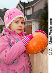 little girl stands in court yard of house and holds pumpkin