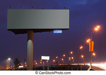 Big gray billboard with illumination at night, road, bridge...