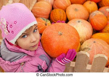Little girl has got pumpkin from big box