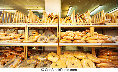lots of fresh crisp loaves of bread on shelves in store;...