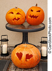 Three pumpkins of Halloween Two lie on glass little table...