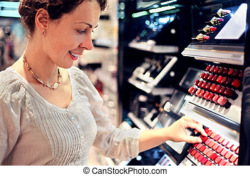 beautiful young woman chooses lipstick in store. bid assortment
