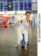 beautiful young woman sitting on their luggage in hall of airport