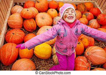 Little girl with drawing on cheek in big box with pumpkins