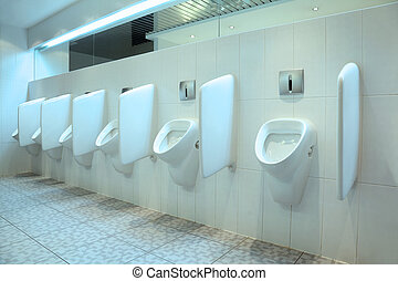 line of six white porcelain urinals in clean, light public...