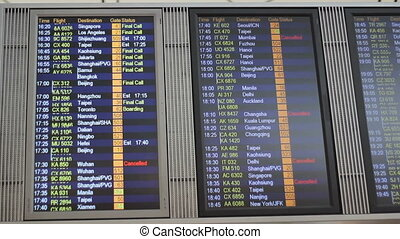 Man Checks Flight Departure Board - An Asian man stops to...
