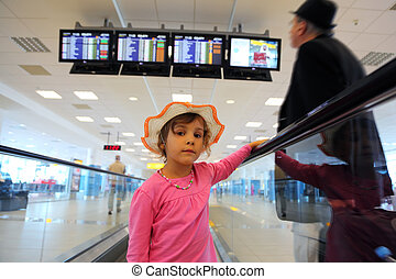 beautiful little girl in hat and pink blouse rides on escalator. old man in black wear. schedule on displays