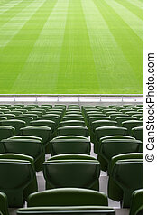 Rows of folded, green, plastic seats in very big, empty...
