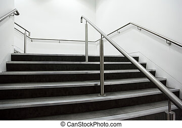 wide staircase with chrome handrails and gray steps, white...