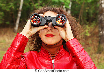 face of beautiful young woman dressed in red jacket looks through binoculars outside