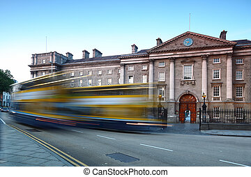 Trinity College at day in Dublin, Ireland. Bus quickly rides...