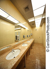 sinks and mirrors in public restrooms, yellow tiles on floor...